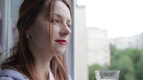 A menina é derramada um vidro do vinho branco Uma moça bebe o vinho branco pela janela filme