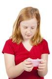 A menina é envio de mensagem de texto em um telefone cor-de-rosa fotografia de stock royalty free