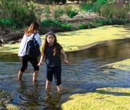 A menina é fria ou congelando-se em um córrego em um parque com a mãe no fundo fotografia de stock