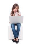A menina é furando e de vista o portátil Fotografia de Stock Royalty Free