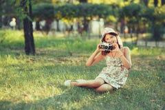 A menina é jogada pela câmera da foto que senta-se na grama no parque Fazendo Selfie e fotografando o mundo ao redor fotos de stock