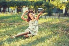A menina é jogada pela câmera da foto que senta-se na grama no parque Fazendo Selfie e fotografando o mundo ao redor imagens de stock
