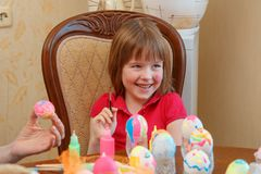A menina é ovos de pintura do divertimento para a Páscoa imagens de stock royalty free
