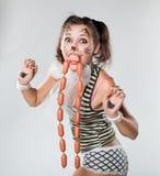 A menina é pintada como um gato Suas salsichas da boca Fotos de Stock Royalty Free