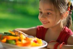 A menina é surpreendida alegre aos vegetais saborosos Imagens de Stock