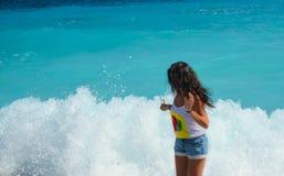 A menina é surpreendida com as ondas borbulhantes Imagem de Stock