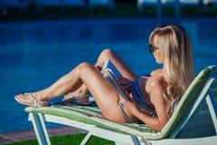A menina é tomando sol e de leitura um livro pela piscina Está vestindo um roupa de banho bonito e uns óculos de sol bonitos Imagens de Stock
