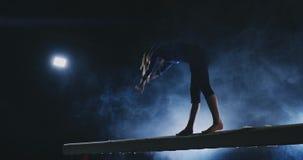 A menina é um atleta profissional executa o truque acrobático ginástico em um feixe no luminoso e no movimento lento nos esportes filme