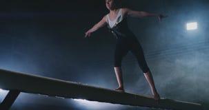 A menina é um atleta profissional executa o truque acrobático ginástico em um feixe no luminoso e no movimento lento nos esportes video estoque