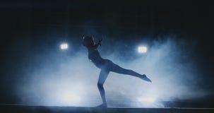 A menina é um atleta profissional executa o truque acrobático ginástico em um feixe no luminoso e no movimento lento nos esportes vídeos de arquivo