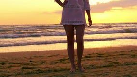 Menina étnica descalça dos pés no vestido branco na praia no por do sol filme