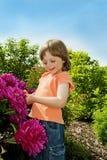 Menina 3 anos de jogo velho com flores Fotografia de Stock Royalty Free