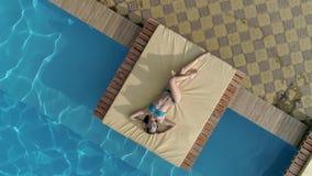 A menina aérea, atrativa no roupa de banho azul e os espetáculos encontram-se perto da piscina no dia de verão filme