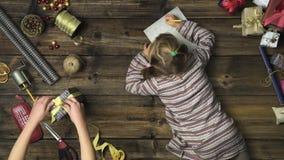 Menina aérea da criança que escreve a letra de Papai Noel na tabela de madeira do vintage quando mum que prepara a caixa de prese filme