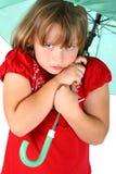 A menina abraça o guarda-chuva no mau tempo isolado imagens de stock royalty free