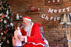 A menina abraça Santa Claus e faz o desejo para o Natal no coz Fotografia de Stock