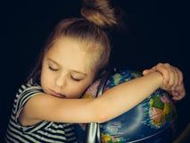 A menina abraçam o globo e calmamente adormecido bonitos Fotografia de Stock