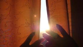 A menina abre as cortinas no amanhecer Os raios do sol passam através da janela e dos dedos