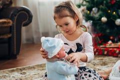 A menina abre o presente do Natal fotografia de stock
