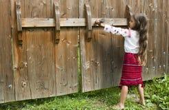 A menina abre a porta Fotografia de Stock Royalty Free