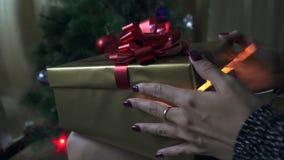 A menina abre um presente perto da árvore de Natal video estoque