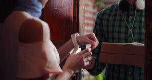 A menina aceita o pacote do correio e faz o pagamento usando o terminal e o cartão vídeos de arquivo