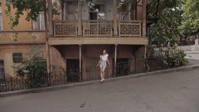 A menina admira a vista de ruas de Tbilisi, Geórgia Arquitetura típica da parte velha da cidade video estoque