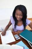 Menina adolescente afro-americana de sorriso que faz seus trabalhos de casa Imagens de Stock Royalty Free
