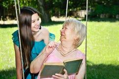 A menina adolescente alegre de riso e sua avó leram um livro em t fotografia de stock royalty free