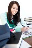 Menina adolescente alegre que estuda em uma mesa foto de stock