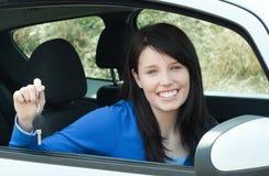 Menina adolescente alegre que senta-se em suas chaves da terra arrendada do carro foto de stock