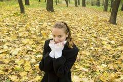 A menina adolescente aquece-se no parque frio do outono Imagens de Stock