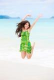 Menina adolescente biracial bonita que salta no ar na praia havaiana Imagem de Stock Royalty Free