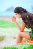 Menina adolescente biracial bonita que senta-se na praia tropical, rezando Fotografia de Stock