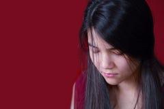 Menina adolescente bonita, biracial que olha para baixo, comprimido ou triste, sobre Foto de Stock Royalty Free