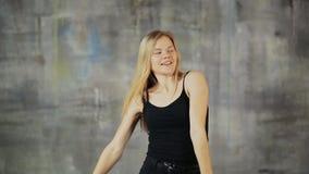 Menina adolescente bonita do cabelo louro que dança hiphop na parede cinzenta Ativamente trabalhos com mãos vídeos de arquivo