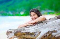 Menina adolescente bonita na praia que relaxa pelo log da madeira lançada à costa Imagem de Stock