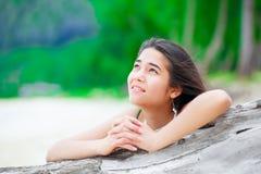 Menina adolescente bonita na praia que reza pelo log da madeira lançada à costa Foto de Stock Royalty Free