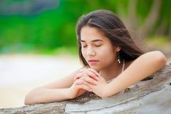 Menina adolescente bonita na praia que reza pelo log da madeira lançada à costa Imagens de Stock Royalty Free