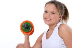 Menina adolescente bonita na roupa do exercício com pesos da mão fotografia de stock