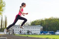 A menina adolescente bonita na roupa dos esportes fotografou no salto no estádio fotografia de stock royalty free