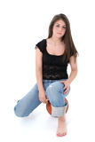 Menina adolescente bonita nas calças de brim que sentam-se na esfera da cesta sobre o branco Imagem de Stock Royalty Free