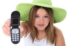 Menina adolescente bonita que entrega o telemóvel à câmera Fotografia de Stock