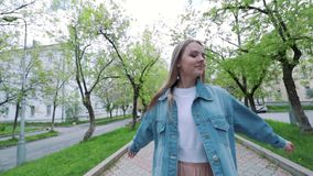 Menina adolescente bonita que escuta a música que anda ao longo das ruas velhas da cidade e da mulher feliz de dança que têm o di filme