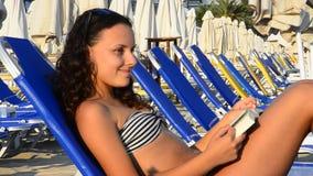 Menina adolescente bonita que lê um livro na praia video estoque