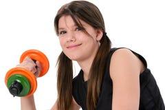 Menina adolescente bonita que prende pesos coloridos sobre o branco imagem de stock