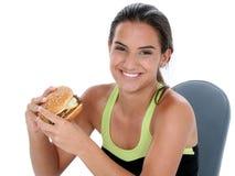 Menina adolescente bonita que prende um cheeseburger gigante Fotografia de Stock Royalty Free