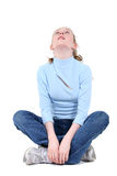 Menina adolescente bonita que senta-se e que olha acima Fotografia de Stock Royalty Free