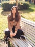 Menina adolescente bonita que senta-se no parque em um banco, sonhando, th imagens de stock royalty free
