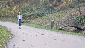 Menina adolescente bonita que skateboarding no parque bonito do outono O conceito da recreação saudável Slowmo filme
